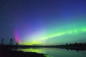 Aurora Borealis glowing green in night sky full of stars, pink colour bursting up